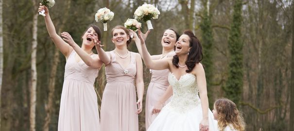 bridesmaids dressed the same way with bouquets smaller than that of the bride's